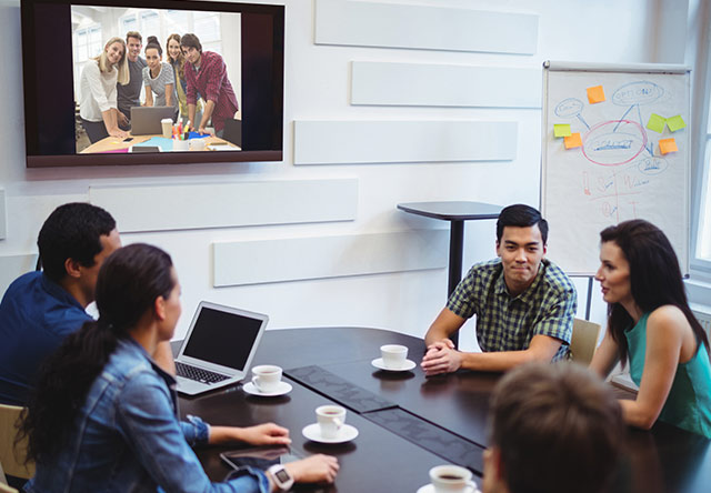 employees in meeting room on a video conference