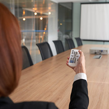 Woman executive switching on office projector