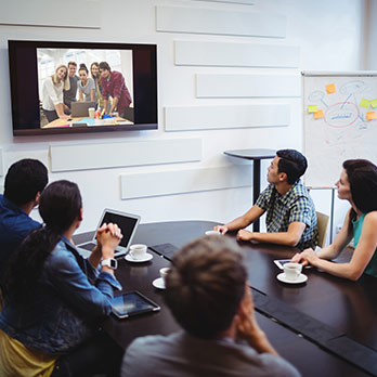 employees in meeting room communicating on video chat